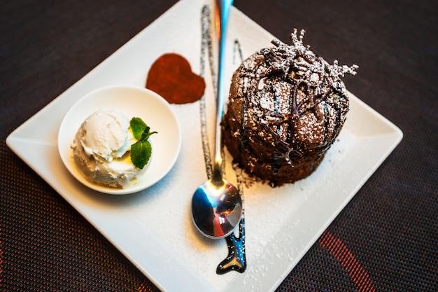 Торт, мороженое, шоколад. шоколадное пирожное с ванильным мороженым и шоколадным сиропом на белой тарелке. выборочный фокус, тонировка. сладкий десерт для шоколадного аромата.