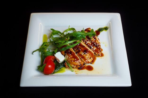 Курица в соусе, посыпанная кунжутом, с помидорами, зеленью и белым сыром. запеченное мясо на белой тарелке на черном фоне