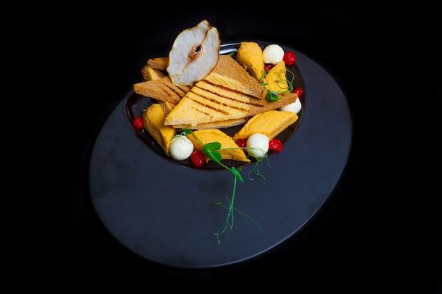 Хлеб из белой и ржаной муки, вареная курица, яйцо, зелень, сушеная груша на черной тарелке. черный фон