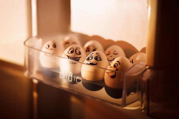 感情的に冷蔵庫のトレイに卵。カートンに配置された顔が描かれた白い卵。卵箱に落書きされた卵。面白い写真。