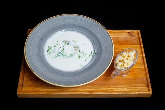 Суп с пюре из белых грибов с зеленью и сухарями на деревянном подносе. черный фон