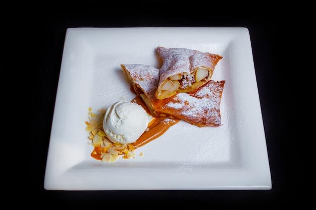 Вкусный сладкий десерт. воздушный яблочный штрудель с сахарной пудрой, шоколадным джемом, тонкими кусочками лесного ореха и порцией белого сливочного мороженого. черный фон
