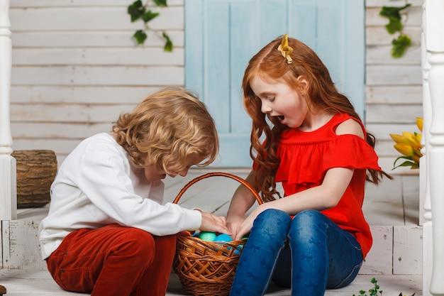 美しい子供たちはイースターエッグのバスケットと一緒に座っています