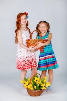 Две девушки держат корзину с пасхальными яйцами