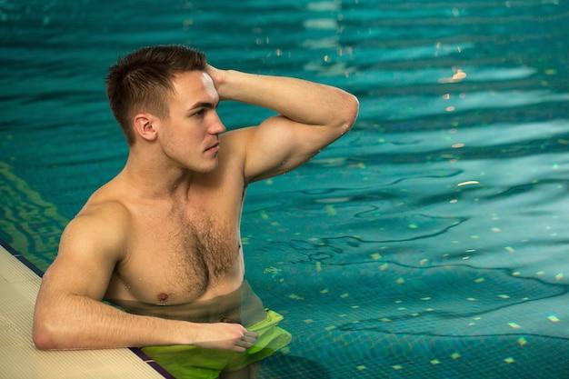 スイミングプールで休んで運動のトーンのボディとハンサムな若い男