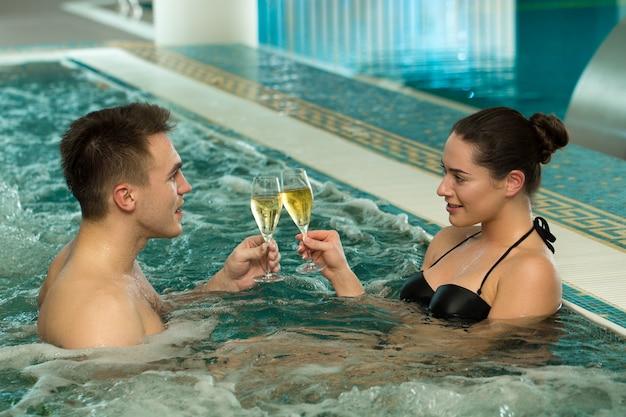 一緒にジャグジー浴槽でリラックスできる美しい愛情のあるカップル