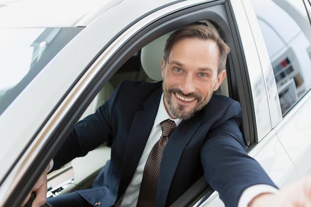 Красивый зрелый человек делает селфи, сидя в своей машине