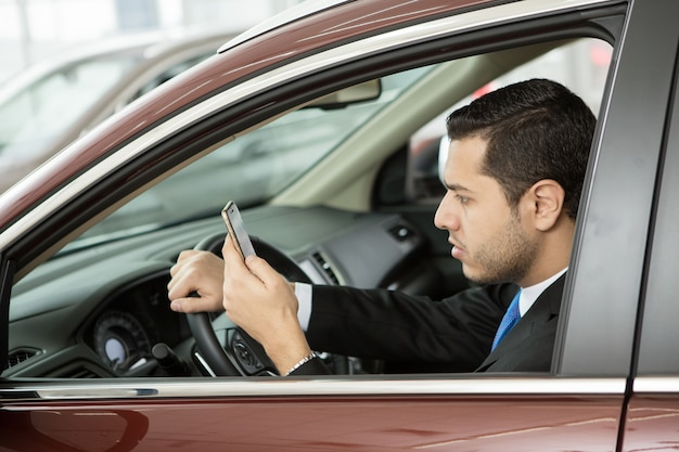 車に座っている彼の電話を使用してハンサムな青年実業家