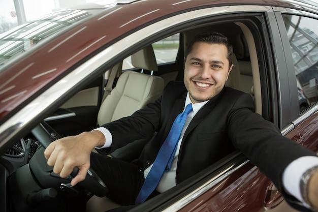 Счастливый мужской водитель делает селфи в своей машине
