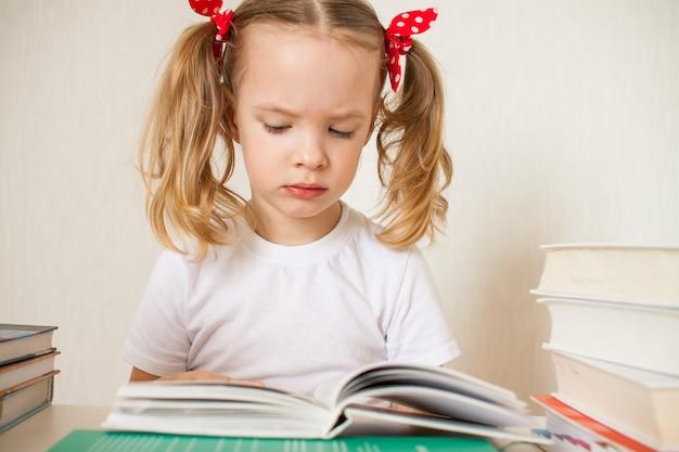Маленькая девочка учится уроки на дому. домашнее обучение