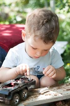夏の路上で小さな男の子がおもちゃの車で遊ぶ