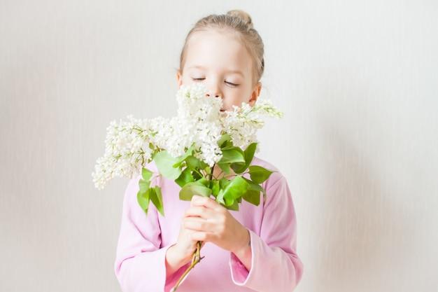 白いライラックの花束を手に持ったかわいい女の子。賞賛、ルックス、母親に与える。母の日