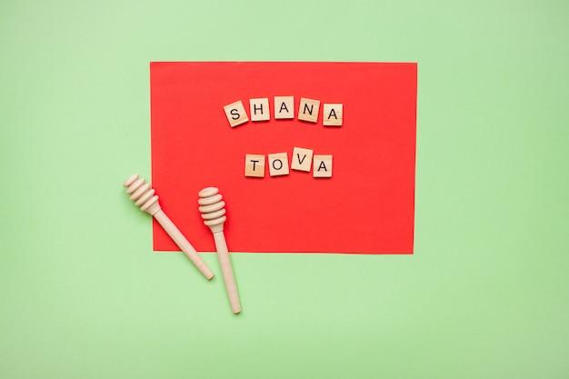 赤と緑の木製ブロック「シャナトバ」と蜂蜜用木製スプーンの言葉。