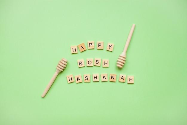 木製のブロックからの言葉「ハッピーロッシュハシャナ」と緑の蜂蜜の木製スプーン