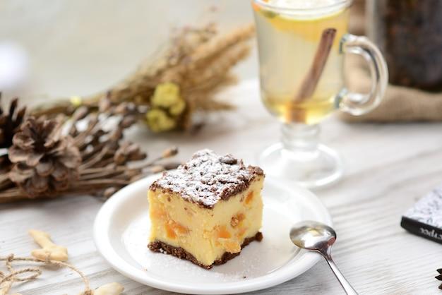 Ломтик простого нью-йоркского чизкейка на белой тарелке на деревянном фоне