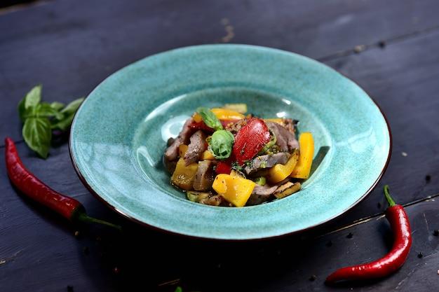 肉、ピーマン、トマト、バジルのサラダ、木のストーブの上のターコイズブループレート