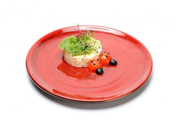 赤い皿にチェリートマトとオリーブの装飾が施されたロシア風サラダ