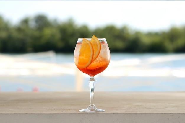 ガラスタンブラーに氷とオレンジのカクテル。花飾り付き