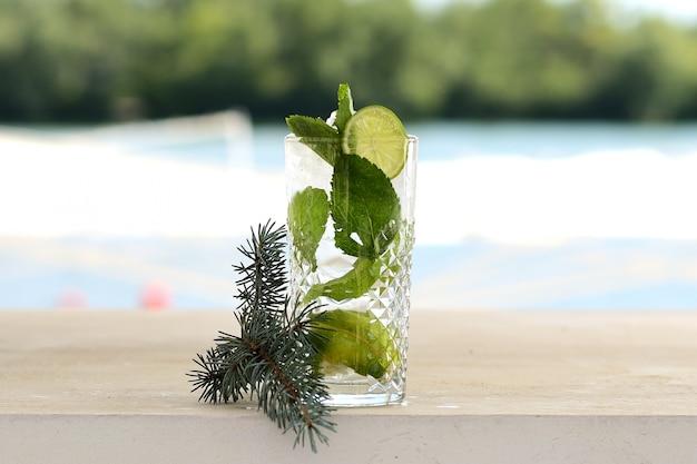 ガラスのタンブラーでミントと氷のカクテル。花とフルーツの装飾付き