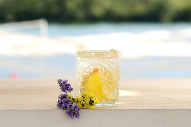 グラスにレモンとミントのカクテル。花飾り付き