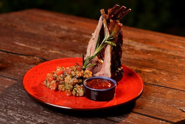 おいしい焼きカルビとソース。木製のテーブルの赤い皿に