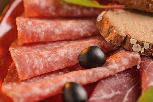 Ассорти колбас, хамон и ветчина с кусочками жареного хлеба на красную тарелку. на деревянном столе