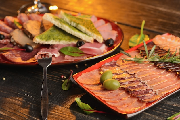 赤いプレートに揚げパンのスライスとソーセージ、ハモン、ハムの盛り合わせ。木製のテーブルの上