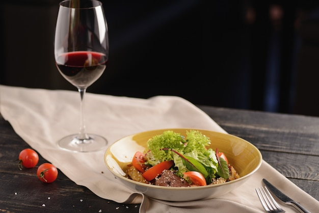 肉、トマト、ゴマ、レタスのサラダ。木製のテーブルの上の黄色のプレートで