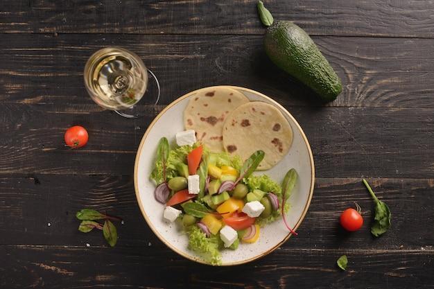 Салат с помидорами, огурцами, сладким перцем, оливками и сыром фета. греческий салат. в белой глиняной тарелке на деревянном столе