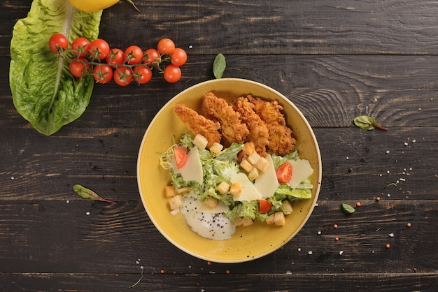 鶏肉、卵、パルメザンチーズ、野菜のシーザーサラダ。木製のテーブルの上の黄色のプレートで