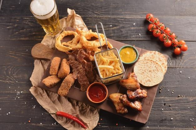 Пивные закуски. жареные куриные крылышки, картофель фри, луковые кольца, сыр в кляре и вяленое мясо. на деревянной доске