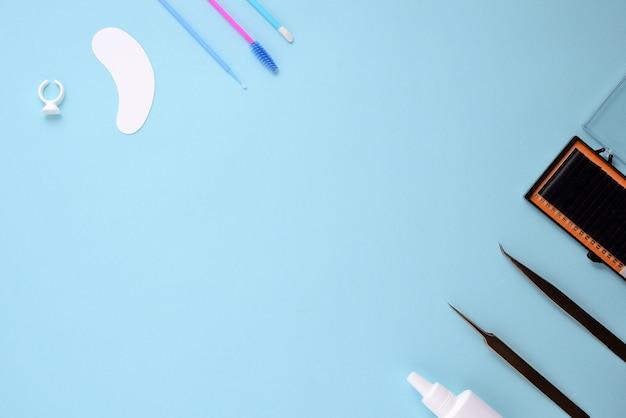 Макияж кисти и косметика на синем фоне. вид сверху, плоская планировка, копирование пространства