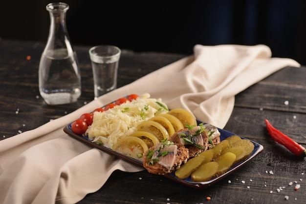 Соленая сельдь с маринованными овощами. на деревянном столе