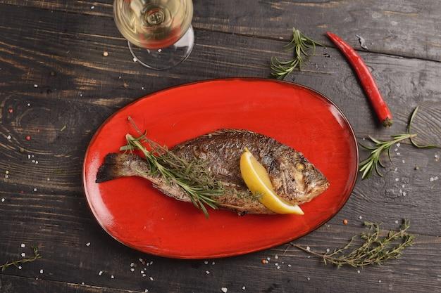 魚のグリル、レモンとローズマリーの小枝。木製のテーブルの赤い皿に