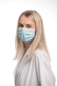 白い背景の上の医療マスクでブロンドの髪を持つ美しい少女