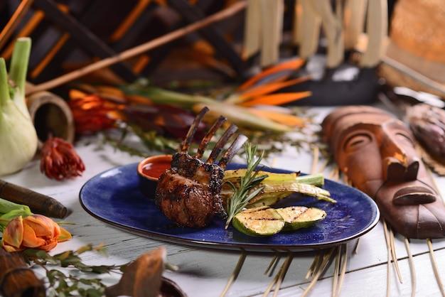 焼きたての野菜とソースの子羊のラック。ブループレートに