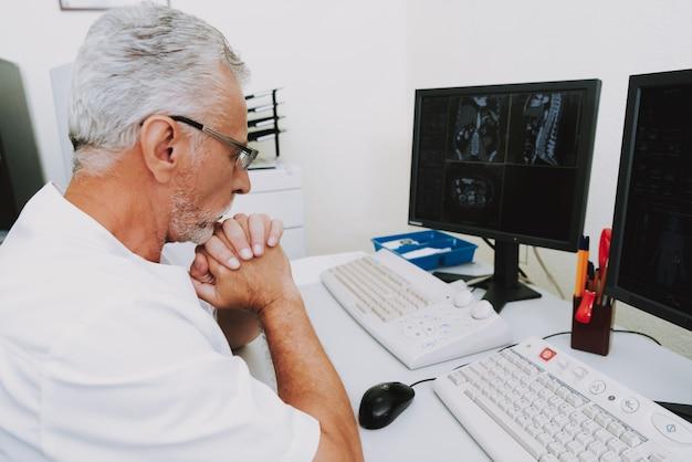 Концентрированный доктор рентгенологии, изучающий компьютерную томографию
