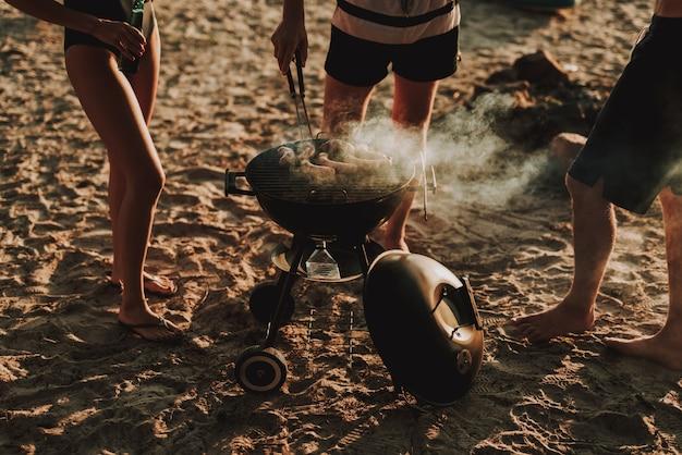 ビーチパーティーのコンセプトです。男はバーベキューソーセージを焼きます。