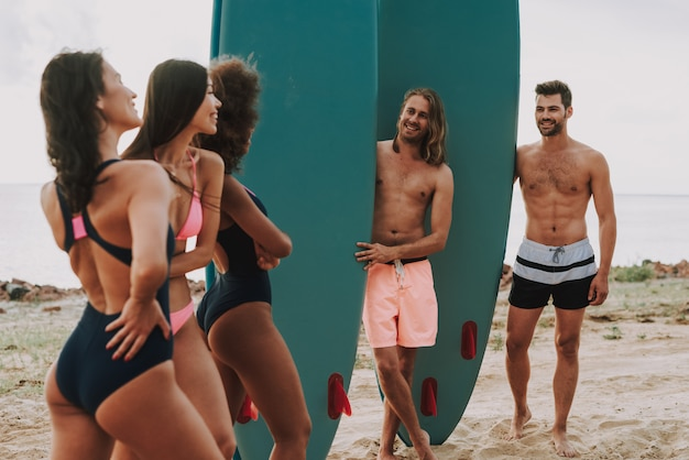 ビーチで二人の男はサーフを保持しています。ビーチで水着の女の子。
