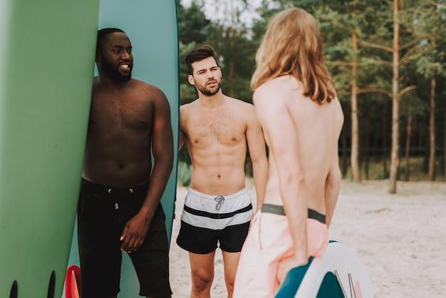 サーフィンをしている若い人たちはビーチで話しています。