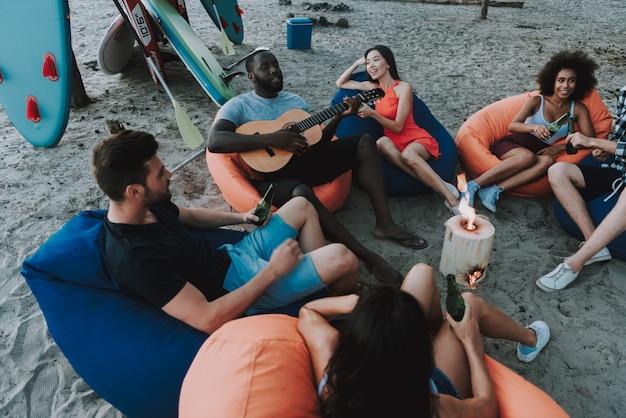 アフロアメリカンの人々はビーチパーティーでギターを弾きます。