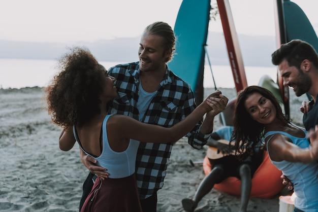 カップルはビーチで踊ります。アメリカのギタリスト。