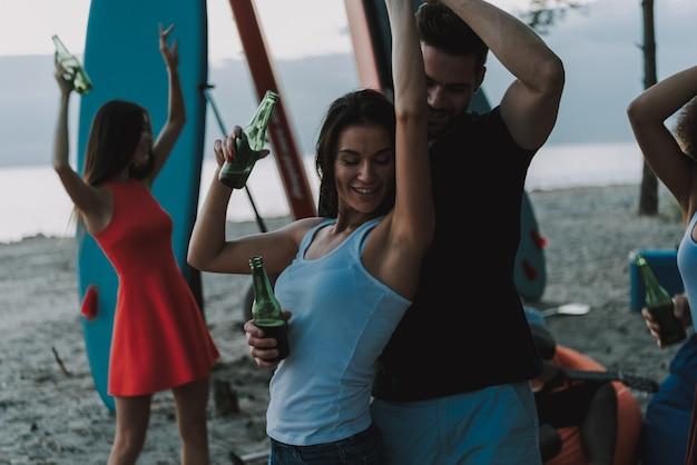 人々は一緒にビーチで踊っています。