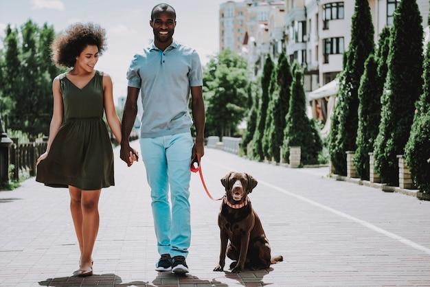 Счастливая пара афроамериканцев гуляет с собакой