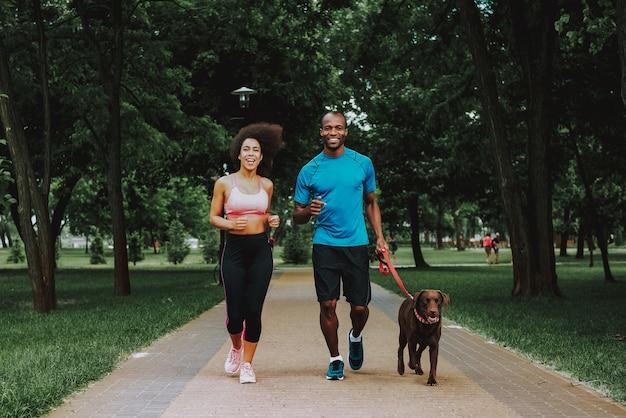 犬を遊んでスポーツウェアのアフリカ系アメリカ人カップル