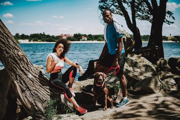 Афроамериканец пара на берегу реки с собакой