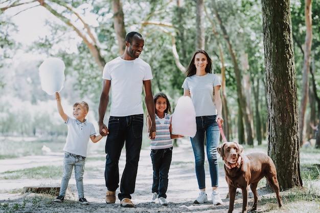 Родители и дети гуляют по парку с собакой