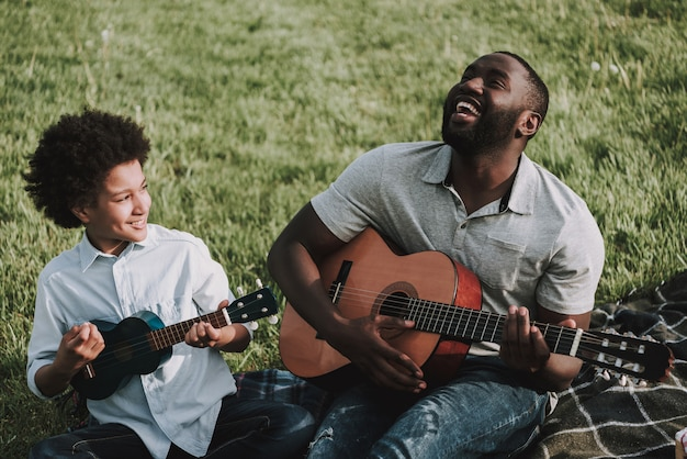 Отец и сын играют на гитаре на пикнике