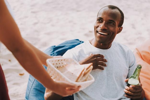 女性はピクニックに幸せな男にサンドイッチを提供しています