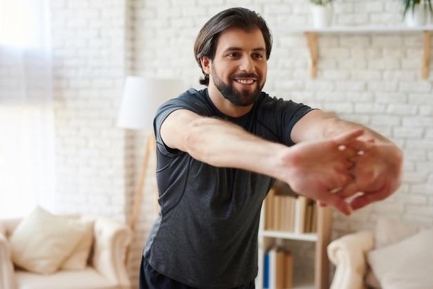 ストレッチ指をしているハンサムな男が自宅で運動します。